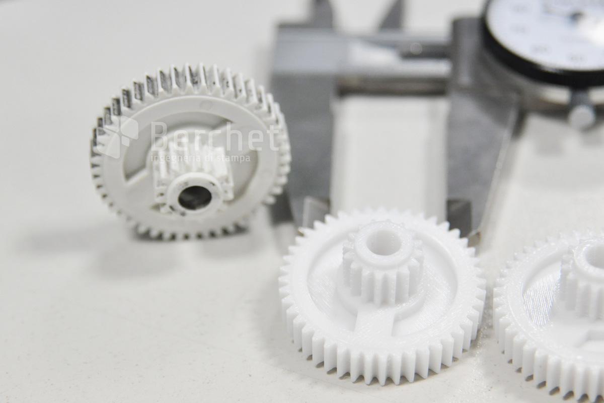 Un ingranaggio usurato, accanto a una sua riproduzione stampata in 3D e un calibro.